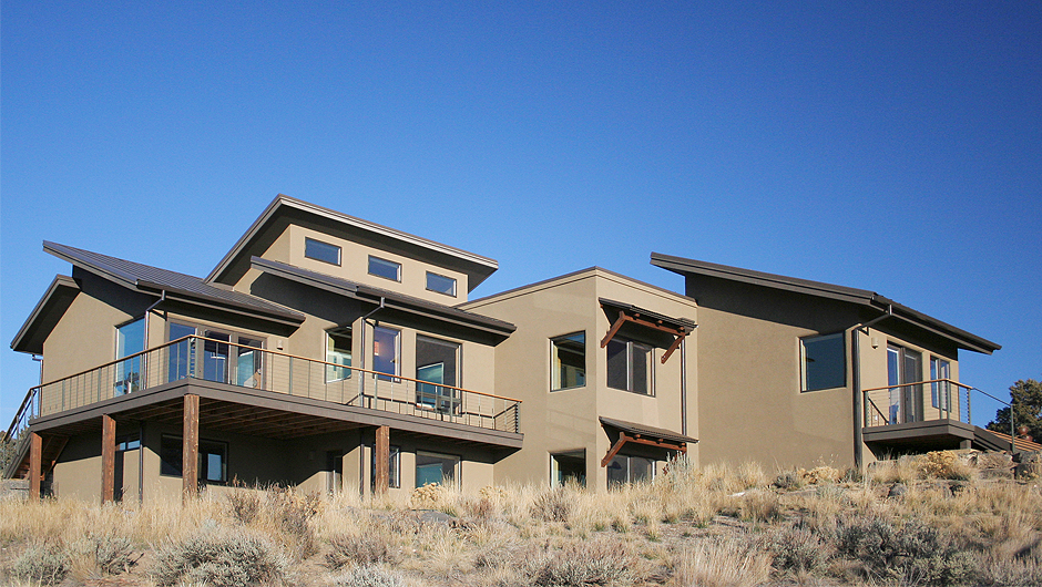 Southwest elevation with large south facing windows, protective awnings, large Trex decks, and criss crossed roofs
